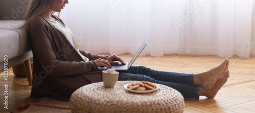 Young woman typing on laptop, resting on floor at home Fototapet
