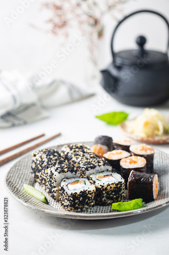 Fototapeta Set of sushi and maki on plate with soy sauce and chopsticks on white background. Top view with copy space obraz