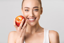 Woman With Perfect Smile Holding Apple Posing On Gray Background
