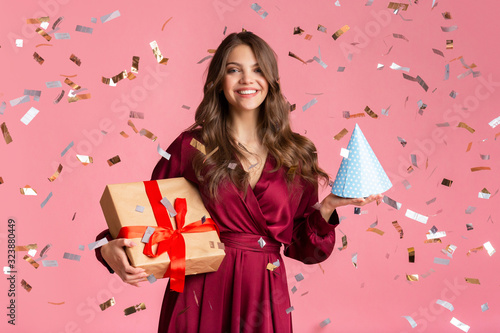 Happy girl with gift box and birthday hat under confetti rain