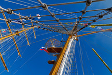Mast Sailing Ship With Flags Of Russia And Other Countries Against The Blue Sky Perspective View From Below