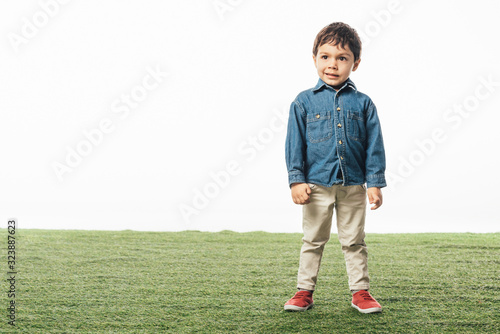 smiling and cute boy standing on grass isolated on white