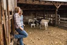 Two Young Cowgirls Leaning Against Barn In Animal Pen. Bridger, Montana, USA