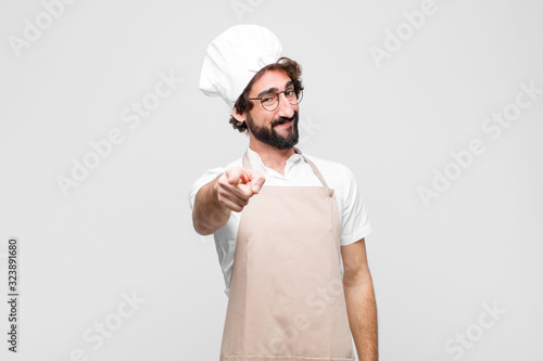 Obraz young crazy chef pointing at camera with a satisfied, confident, friendly smile, choosing you against white wall - fototapety do salonu
