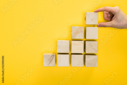 top view of man holding wooden cube isolated on yellow