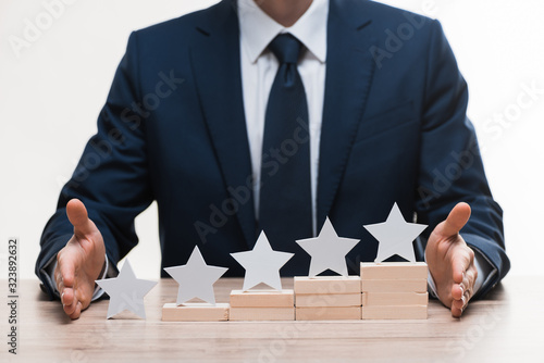 cropped view of businessman in formal wear near blocks with stars isolated on white, quality concept