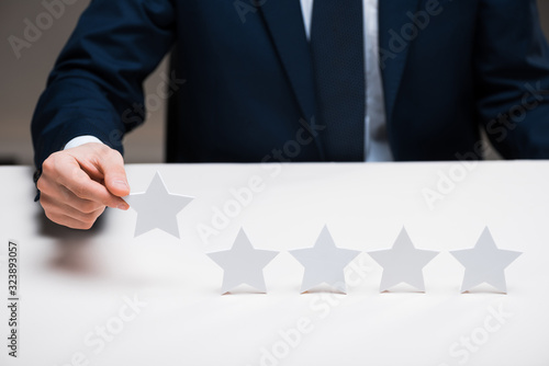 cropped view of businessman in suit holding star on grey, quality concept