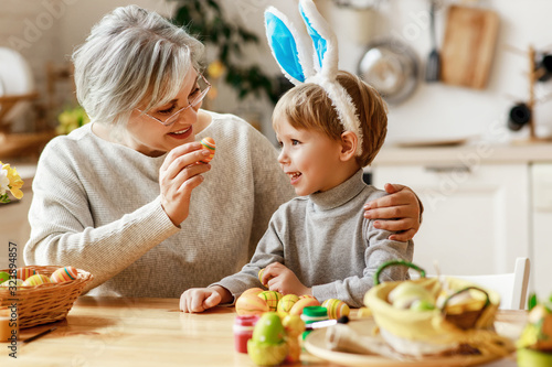 Happy easter! family grandmother and child with ears hare getting ready for holiday.