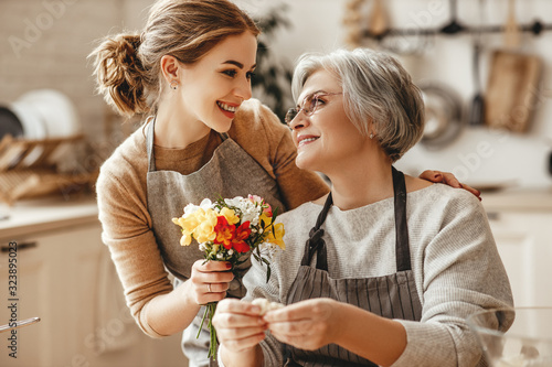 happy mother's day! family old grandmother  mother-in-law and daughter-in-law daughter congratulate on   holiday, give flowers .