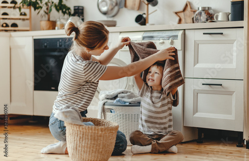 Obraz Happy family mother housewife and child   in laundry with washing machine . - fototapety do salonu
