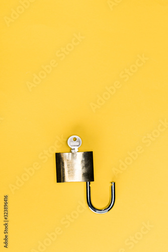 top view of metallic key in locker isolated on yellow