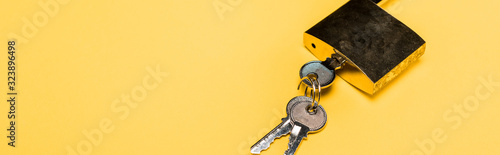 panoramic shot of metallic padlock with keys isolated on yellow