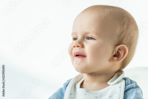 Cute baby boy with soiled mouth looking away on white background