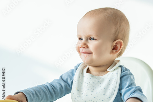 Smiling baby boy with soiled mouth sitting on feeding chair on white background