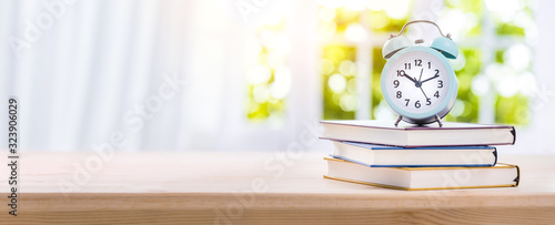 Stack of Books with Alarm Clock on Wooden Desk Canvas Print