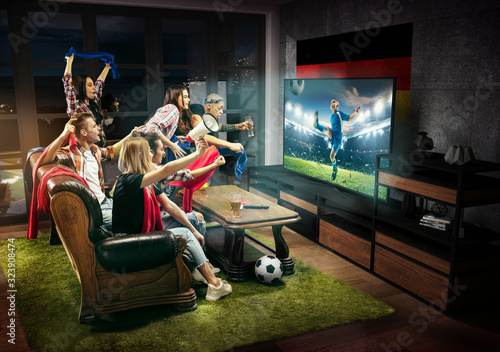 Group of friends watching TV, match, championship, sport games. Emotional men and women cheering for favourite teens football team of Germany with flag. Concept of friendship, competition, emotions.
