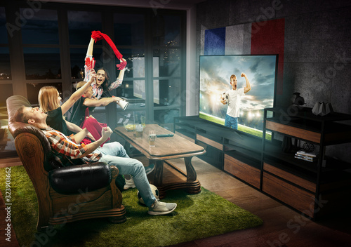 Group of friends watching TV, teens football match, championship, sport games. Emotional men and women cheering for favourite soccer team of France. Concept of friendship, sport, competition, emotions