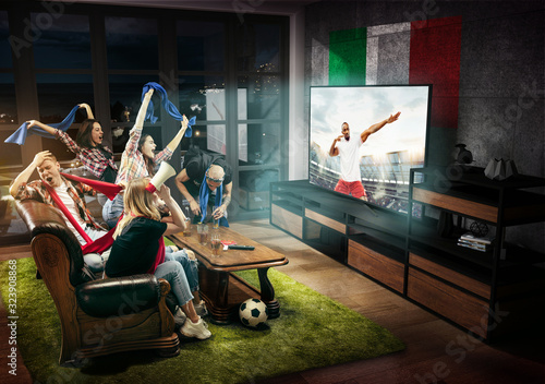 Group of friends watching TV, match, championship, sport games. Emotional men and women cheering for favourite football team of Italy with national flag. Concept of friendship, competition, emotions.