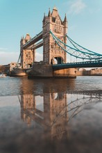 Tower Bridge In London Reflected In The Wet Stone Wall Along The River Thames