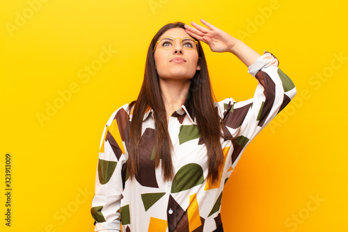 Fototapeta young pretty woman greeting the camera with a military salute in an act of honor and patriotism, showing respect against yellow wall obraz