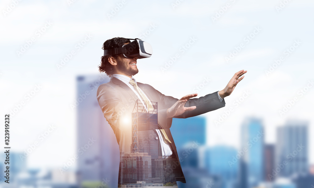 Fototapeta Handsome elegant businessman experiencing impressive virtual reality and business city at backdrop