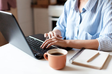 Freelancer workplace with laptop, cup of coffee and notebook. Young woman working from home office in cozy kitchen. Female business. Close up of hands.