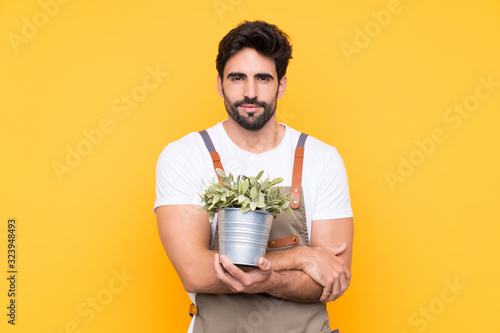 Foto Gardener man with beard over isolated yellow background keeping arms crossed