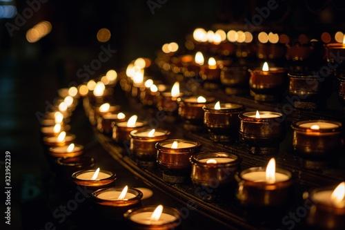 Fotografia Closeup shot of prayer candles with dark background
