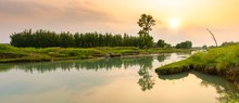 Panorama Of A River Surrounded By Greenery With Trees Reflecting On The Water During The Sunset