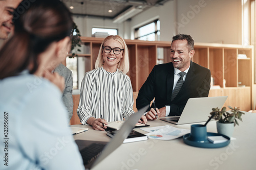 Laughing group of businesspeople working around an office table Fototapet