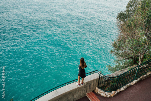 Happy girl enjoying the Mediterranean sea standing at the cliff on Cote d'Azur, France, luxury recreation place Wallpaper Mural