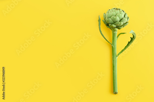 Photo Fresh green artichoke on yellow background