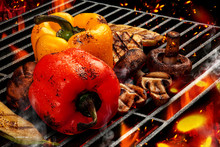 Process Of Preparing Red And Yellow Bell Pepper, Zucchini, Champignons On Barbecue Bbq Grill. Flaming Fire, Ember Charcoal And Smoke. Close Up