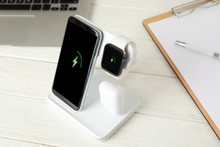 Set Of Gadgets Charging With Wireless Device On White Wooden Table