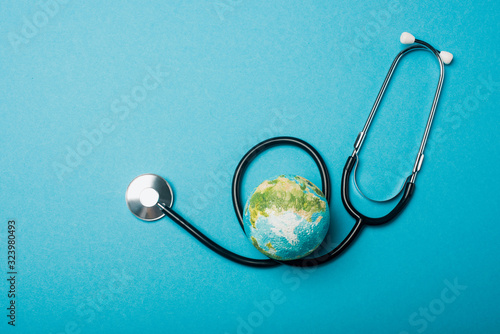 Top view of globe and stethoscope on blue background, world health day concept