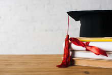Diploma With Beautiful Bow, Graduation Cap With Red Tassel On Top Of Books On Table On White Background
