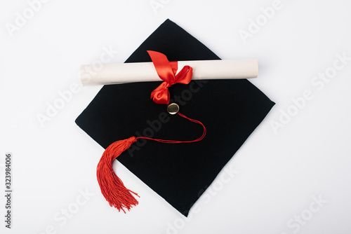 Top view of black graduation cap with red tassel and diploma on white background