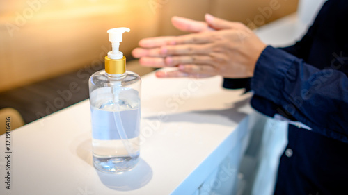 Photo Washing hands by alcohol sanitizers or alcohol gel from pump bottle in public area