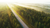 Fototapeta  - Aerial view of a highway with cars covered in fog. Early misty morning. Beautiful forest and sun rays.  Spotted from above with a drone. Finland, Europe.