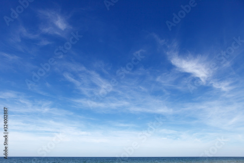 Beautiful blue sky with cirrus clouds over the sea. Skyline. - 324002887