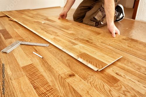 Obraz A craftsman lays oak parquet with a click system - fototapety do salonu