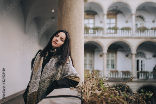 Photo A young black-haired girl in a dark autumn coat and a wide scarf-wrap stands on the balcony with a colonnade and looks looking at the viewer