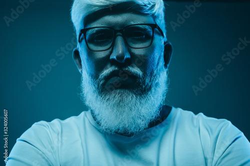 Serious albino man in dark neon light Fototapet