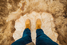 From Above Top View Of Anonymous Person Legs In Brown Boots And Blue Jeans Standing On Dirty Sandy Road With Mountain And Sky On Blurred Background In Bardenas Reales, Navarre, Spain
