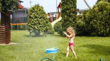 Little Girl Playing With Water In The Yard Of The House