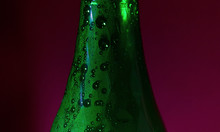 Drops Of Water On The Green Bottle Of Beer On Red Blurred Background