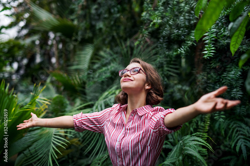 Young woman standing in botanical garden, arms stretched. - 324025859