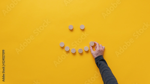 Making a smiling face of blank wooden cut circles Canvas Print