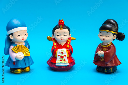 Three decorative ceramic Korean figures in traditional colorful clothes Han bock Figures are allocated over a turquoise background Wallpaper Mural