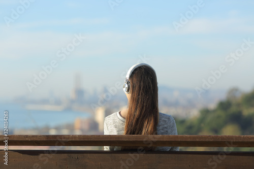Photo Woman wearing headphones listening to music on a bench